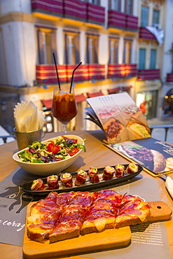 View of traditional Spanish tapas overlooking Plaza del Siglo at dusk, Malaga, Costa del Sol, Andalusia, Spain, Europe