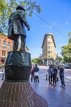 Statue and visitors in Maple Tree Square in Gastown, Vancouver, British Columbia, Canada, North America