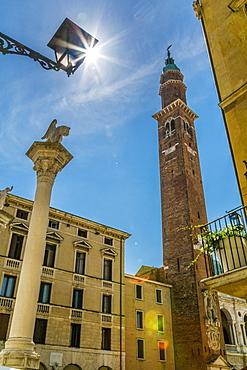 Sun peeking from street lamp and clock tower of Palladian Basilica in Piazza Signori, Vicenza, Veneto, Italy, Europe