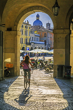 View of cyclist and Piazza delle Erbe through archways and dome of Padua Catherdal visible, Padua, Veneto, Italy, Europe