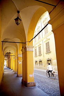 Arcade and cyclist, Modena, Emilia Romagna, Italy, Europe