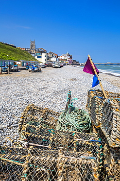 View of fishing baskets on the beach and Parish Church overlooking pier on a summer day, Cromer, Norfolk, England, United Kingdom, Europe