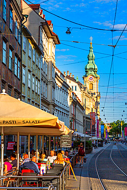 View of Parish Church of the Holy Blood and cafes, Graz, Styria, Austria. Europe