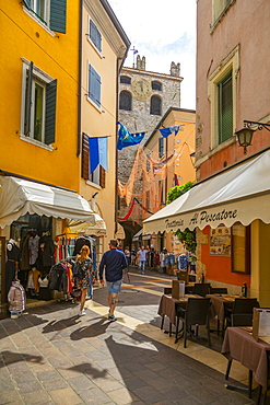 View of cafes and visitors on narrow street on a sunny day, Garda, Lake Garda, Province of Verona, Veneto, Italian Lakes, Italy, Europe