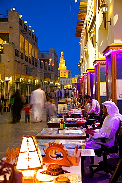 Souq Waqif looking towards the illuminated spiral mosque of the Kassem Darwish Fakhroo Islamic Centre, Doha, Qatar, Middle East