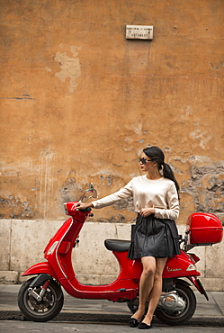 Young woman waiting by Vespa moped, Rome, Lazio, Italy, Europe