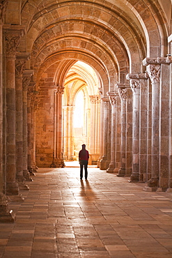 A lady slowly walks down an aisle in the Basilique Sainte-Marie-Madeleine of Vezelay, Yonne, Burgundy, France, Europe