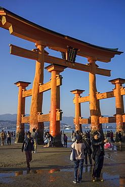 Tourists walking under the torii gate of Miyajima at low tide, Itsukushima, UNESCO World Heritage Site, Hiroshima Prefecture, Honshu, Japan, Asia
