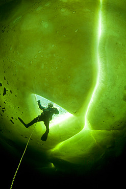 Scuba diver exit the maina (sawed entry hole) to dive under the ice, Arctic circle Dive Center, White Sea, Karelia, northern Russia