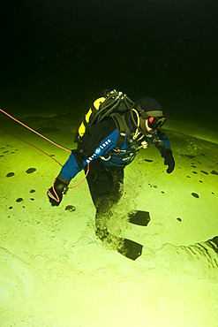 Scuba diver under ice walking upside down, exercise to practice orientation, Arctic circle Dive Center, White Sea, Karelia, northern Russia