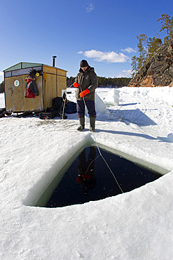 Person who provide contact with the divers inside the maina (sawed entry hole) to dive under the ice, Arctic circle Dive Center, White Sea, Karelia, northern Russia