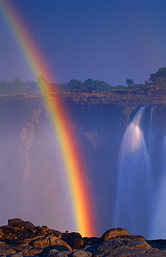 rainbow over waterfall natural phenomenon daytime outdoors vertical format Victoria Falls Zimbabwe Africa