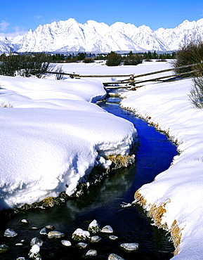 splitrail fence across a stream below the Teton Range in winter Grand Teton National Park Wyoming USA