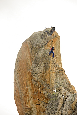 Climbers on a pinnalce on the Aiguille du Midi above Chamonix, France.