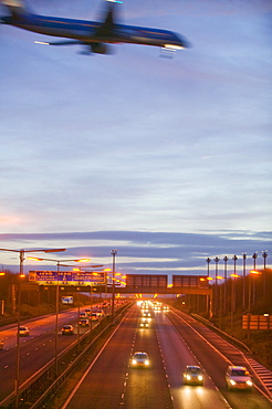 A plane flying over car lights on the M1 motorway in Leicestershire, England, United Kingdom, Europe