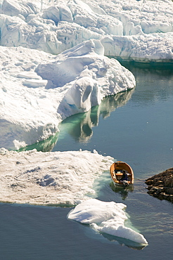 An Inuit fishing boat sails through icebergs from the Jacobshavn glacier (Sermeq Kujalleq), Greenland, Polar Regions