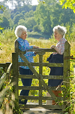Women chatting over a gate in Ambleside, Lake District, Cumbria, England, United Kingdom, Europe