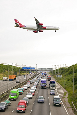 Traffic congestion on the M1 motorway and a plane coming in to land at East Midlands Airport, near Loughborough, Leicestershire, England, United Kingdom, Europe
