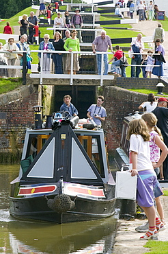 A narrowboat going through Foxton Locks on the Grand Union Canal, the longest series of locks in the UK with visitors on a summer's day, Leicestershire, England, United Kingdom, Europe