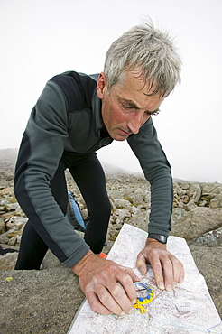 A man navigating on Scafell Pike in the Lake District National Park, Cumbria, England, United Kingdom, Europe