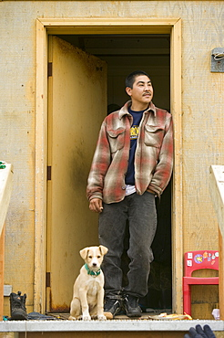 An Inuit man and puppy on Shishmaref, a tiny island inhabited by around 600 Inuits, between Alaska and Siberia in the Chukchi Sea, United States of America, North America