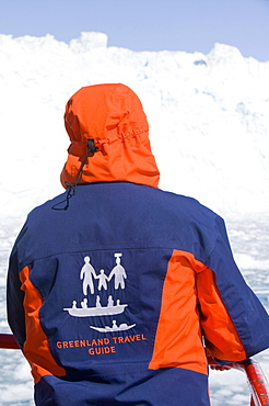 A Greenland tour guide wearing a colourful jacket onboard a ship infront of the Eqi glacier, Greenland, Polar Regions