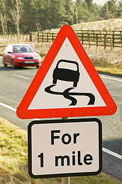 A road warning sign of slippery conditions, England, United Kingdom, Europe