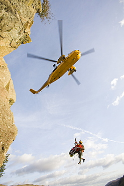 An RAF Sea King helicopter evacuates a seriuosly injured climber with a broken femur from a mountain rescue site in the Langdale Valley, Lake District, England, United Kingdom, Europe