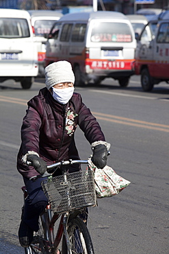 A cyclist wears a face mask against the awful air pollution in Harbin city, Heilongjiang, Northern China, Asia