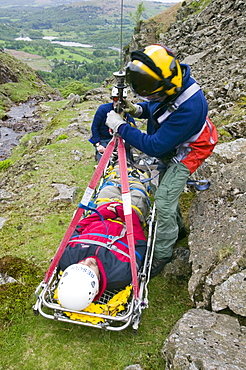 An RAF Sea King Helicopter winchman and casualty on a stretcher, Loughrigg in the Lake District, Cumbria, England, United Kingdom, Europe