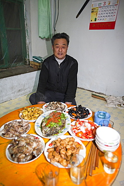 A Chinese man sitting cross legged for a traditional meal in Heilongjiang Province, Northern China, Asia