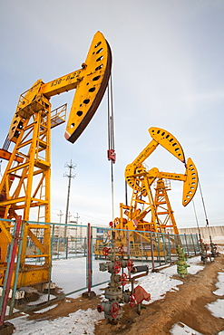 Nodding donkey oil pumps pumping oil up from the Daqing oil field in Northern China, Asia