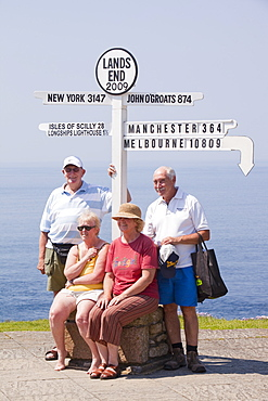 Friends on holiday having their photo taken at Lands End with the distances to the towns where they live, Cornwall, England, United Kingdom, Europe