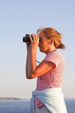 A woman birdwatching off sea cliffs on Cape Cornwall in Cornwall, England, United Kingdom, Europe