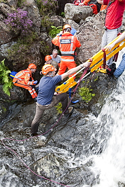 Paramedics from the Great North Air Ambulance and members of Langdale/Ambleside Mountain Rescue Team treat an injured man who fell into Wrynose Beck, before transferring him to hospital via helicopter. Lake District, Cumbria, England, United Kingdom, Europe