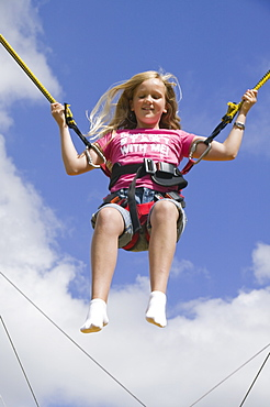 A child on a bungee machine at Ambleside Sports, Lake District, Cumbria, England, United Kingdom, Europe