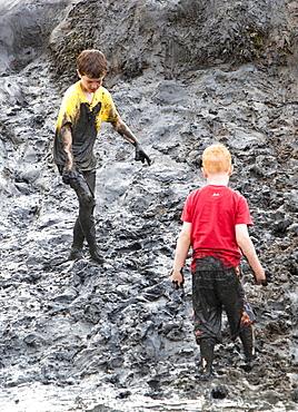 Children playing in a muddy creek at Blakeney, North Norfolk, England, United Kingdom, Europe