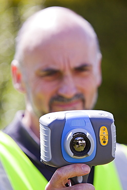 A technician uses a thermal imaging camera to check the thermal efficiency of a house, and where heat is lost from the house, United Kingdom, Europe