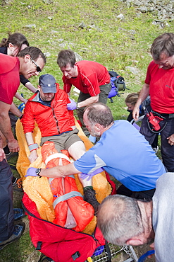 A man with a leg injury is treated by members of the Langdale Ambleside Mountain Rescue Team before being evacuated by air ambulance, above Grasmere, Lake District, Cumbria, Engalnd, United Kingdom, Europe