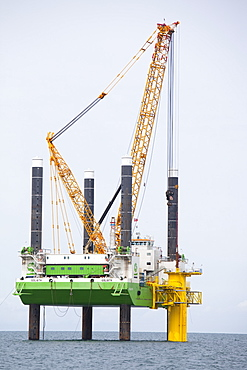 The jack up barge that hammers the monopiles into the sea bed fits a transition piece onto the top of the monopile, Walney Offshore Wind Farm, Cumbria, England, United Kingdom, Europe