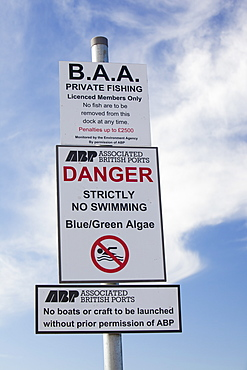 A warning sign about Blue Green Algae in Cavendish Dock in Barrow in Furness, Cumbria, England, United Kingdom, Europe