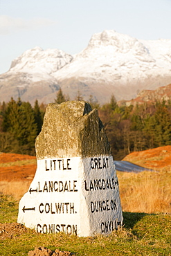 An old stone road sign in the Langdale valley at Elterwater looking towards the Langdale Pikes, Lake District National Park, Cumbria, England, United Kingdom, Europe
