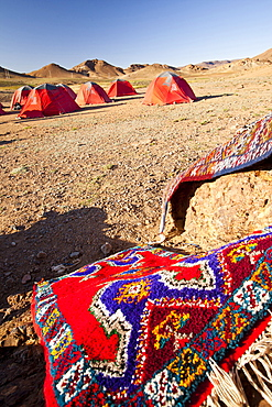 Berber Moroccan woven cloth rugs and bags in front of a trekking campsite in the Anti Atlas mountains of Morocco, North Africa, Africa