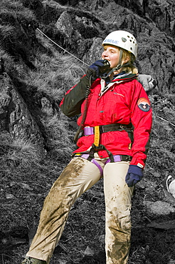 A female member of a mountain rescue team on the radio, Lake District, Cumbria, England, United Kingdom, Europe