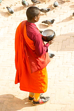 A Buddhist monk collecting donations at the Boudhanath Stupa, one of the holiest Buddhist sites in Kathmandu, Nepal, Asia