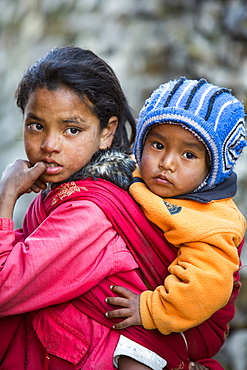 A young Nepalese girl with her baby brother in the Himalayas, Nepal, Asia