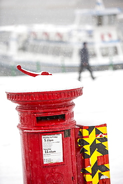 A post box in heavy snow at Ambleside Pier, Waterhead on Lake Windermere, Lake District, Cumbria, England, United Kingdom, Europe