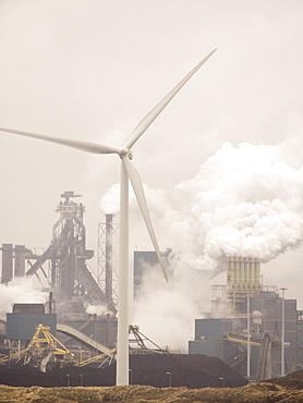 Climate change heaven and hell, emissions from a Tata steel works in Ijmuiden, with a wind turbine, Netherlands, Europe