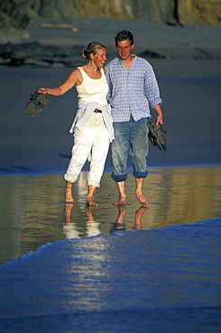 Couple walking at water's edge, Marloes Sands, West Wales, UK