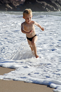 Boy running at water's edge, West Dale